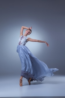 The beautiful ballerina dancing in long blue dress on blue background