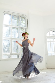 Beautiful ballerina dancing in long gray dress