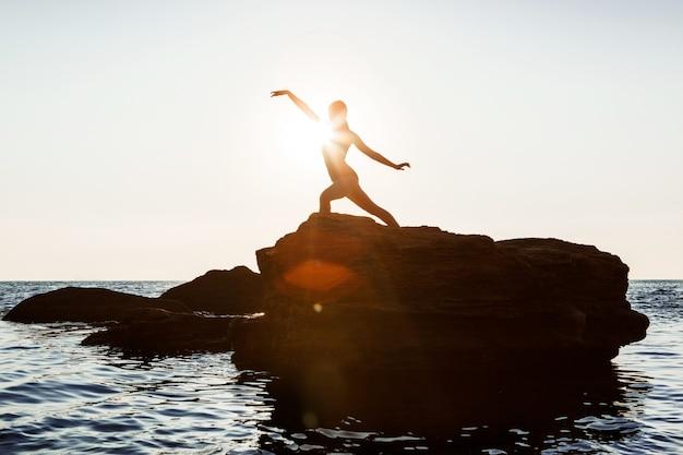 Красивая балерина танцует, позирует на скале на пляже, вид на море.