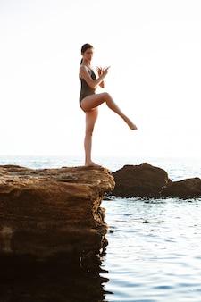 Красивая балерина танцует, позирует на скале на пляже