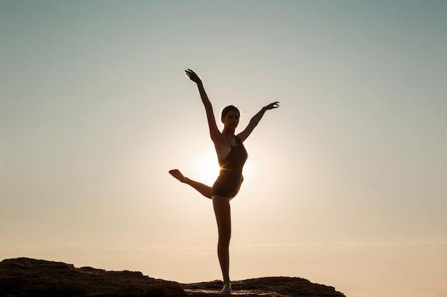 Bella ballerina danza, posa su roccia in spiaggia, vista sul mare.