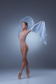 The beautiful ballerina dancing with blue veil on blue background