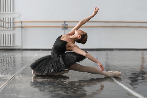 Красивая балерина сидит на шпагате в классе