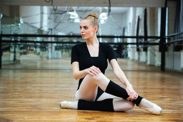 Beautiful ballerina sitting on the floor and looking away in ballet class