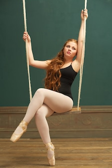 Beautiful ballerina sitting on swing