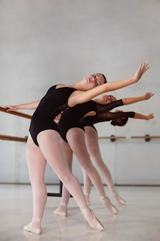 Beautiful ballerinas rehearsing together while wearing leotards