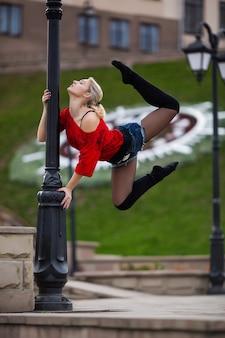 Красивая балерина или акробатический танец на открытом воздухе на улице