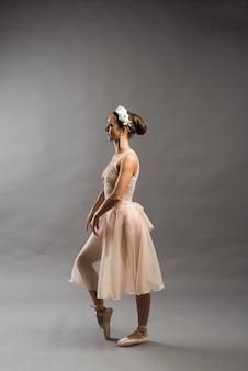 밝은 회색 스튜디오 배경에 포인트 포즈를 취하는 아름다운 발레 댄서