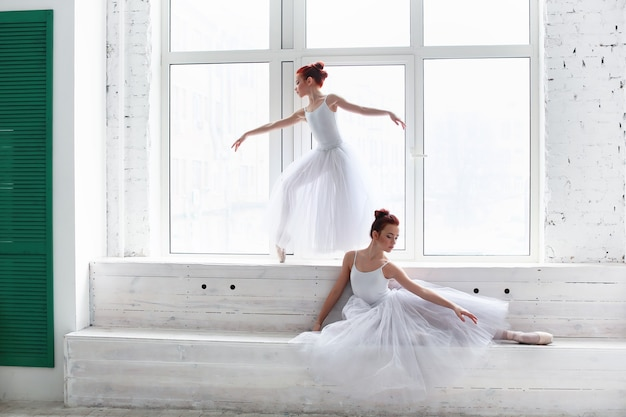 Beautiful ballet dancers in a white room