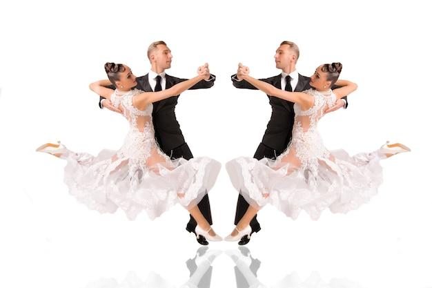 Пара красивых бальных танцев в позе танца, изолированные на белом фоне. чувственные профессиональные танцоры танцуют вальс, танго, медленный фокс и квикстеп