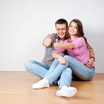 カメラに笑顔のリビングルームで木の床に白い壁にもたれて座っているカジュアルなジーンズの美しい裸足の若いカップル