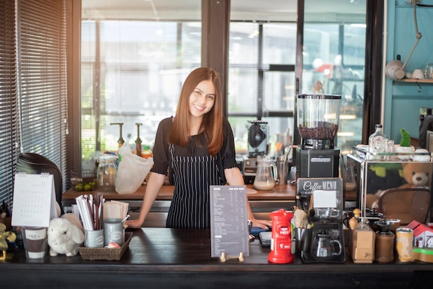 Beautiful barista is smiling  in her coffee shop