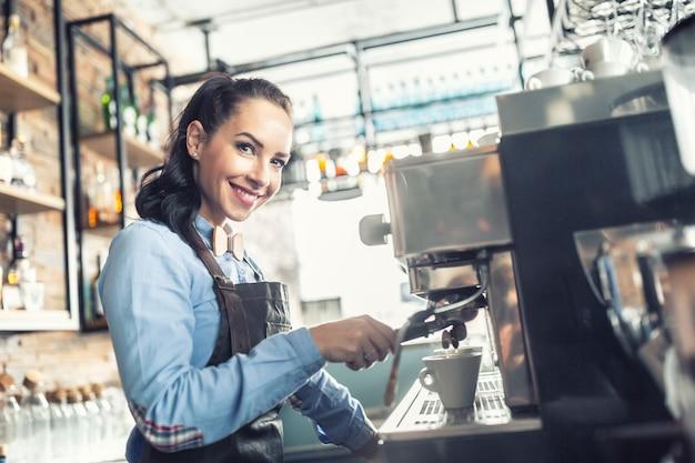 美しいバリスタがカフェのプロのコーヒーメーカーでエスプレッソを作ります。