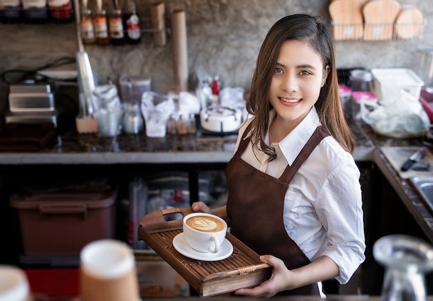 Beautiful barista wearing brown apron holding hot coffee cup served to customer with smili