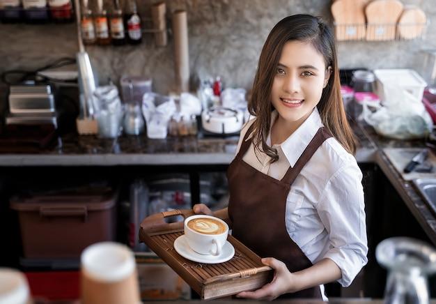 뜨거운 커피 컵을 들고 갈색 앞치마를 입고 아름다운 바리 스타는 smili와 고객에게 제공
