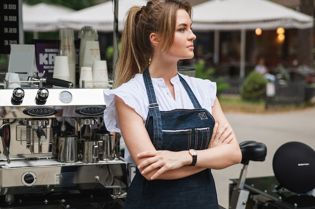 Beautiful barista woman during work in her movable street coffee shop