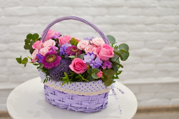 Beautiful basket with fresh flowers on the white table.