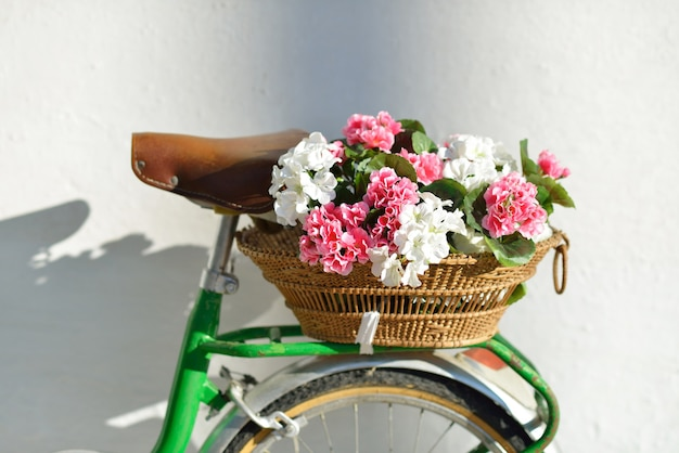 Beautiful basket with geraniums on a vintage bicycle