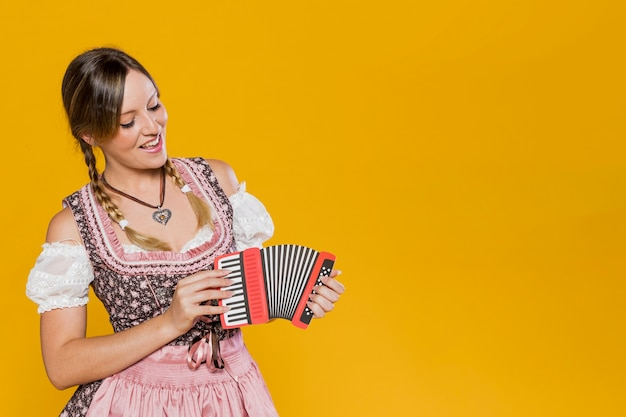 Красивая баварская девушка с бумажным аккордеоном