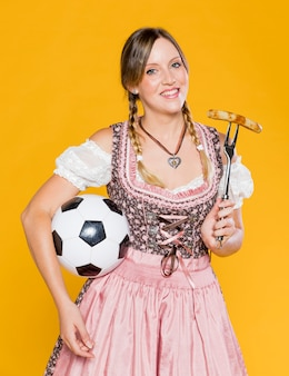 Beautiful bavarian woman with football