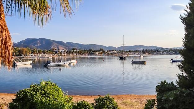 穏やかな水砂浜のビーチボートとヨットの小さな町と緑豊かな山々のある美しい湾