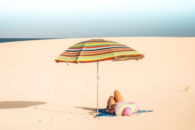 美しいビーチと白人女性が色付きの傘の下で日光浴を楽しんで横になります