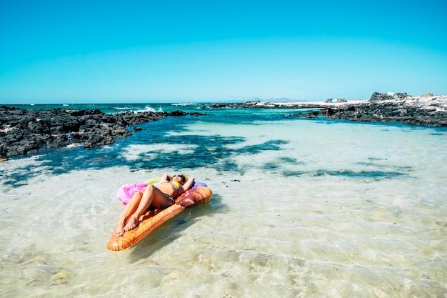 Красивый пляж и тропическая вода океана с красивой женщиной, лежащей на красочном надувном матрасе, лило расслабляется и наслаждается морской природой и пляжем во время летних каникул.