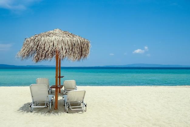 Красивые шезлонги на берегу моря в греции на фоне природы