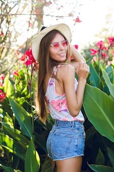 麦わら帽子、ピンクの眼鏡、デニムショートパンツ、明るいtシャツを着て公園に立っている美しいビーチの女の子。女の子はとてもスリムで魅力的です。彼女は遊び心に見える。彼女は熱帯の花の中に立っています