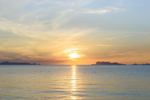 青い海と黄金の光空雲と美しいビーチの夕日