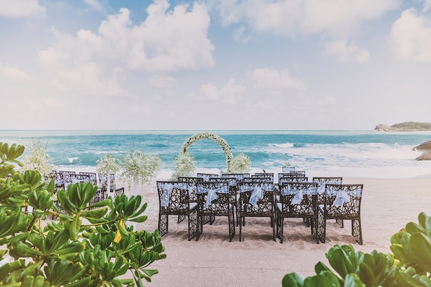 Beautiful beach wedding venue setting with flowers decoration on arch