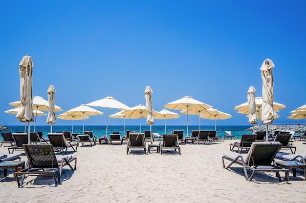 アラビア湾の海岸に傘を持つ美しいビーチ。ドバイ。