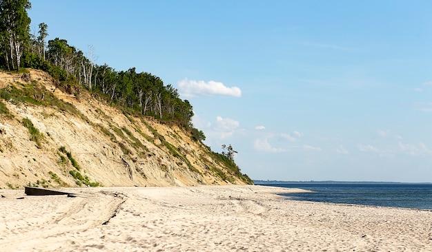Красивый пляж с мелким песком и крутым берегом.