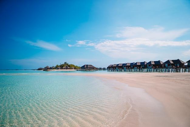 야자수와 변덕 하늘이 아름 다운 해변. 여름 휴가 여행 휴가 배경 개념. 몰디브 파라다이스 비치.