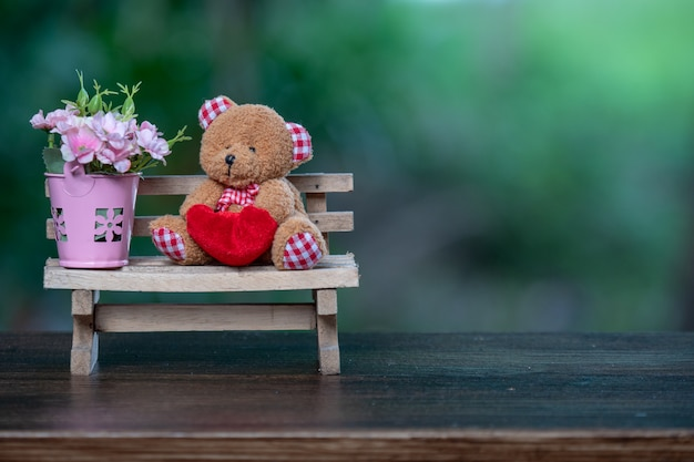 Beautiful bear doll with flowers in vase put on the wooden bench.