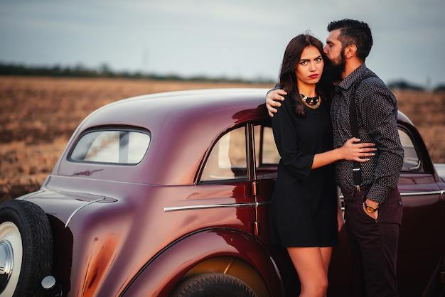 シャツとサスペンダーのズボンを着た美しいひげを生やしたブルネットの男は、フィールドの背景にある茶色のレトロな車の近くにある黒い短いドレスを着た長い髪の細い若い女の子を着ています