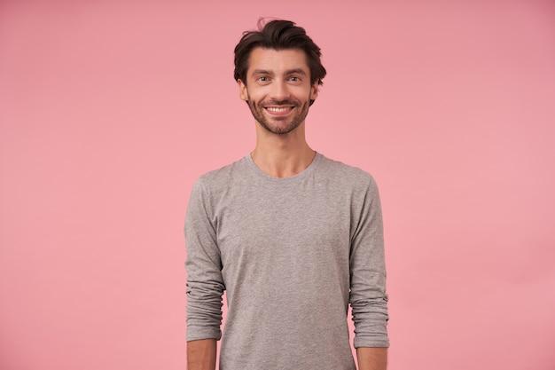 Красивый бородатый мужчина с темными волосами стоит, в повседневной одежде, весело смотрит с опущенными руками