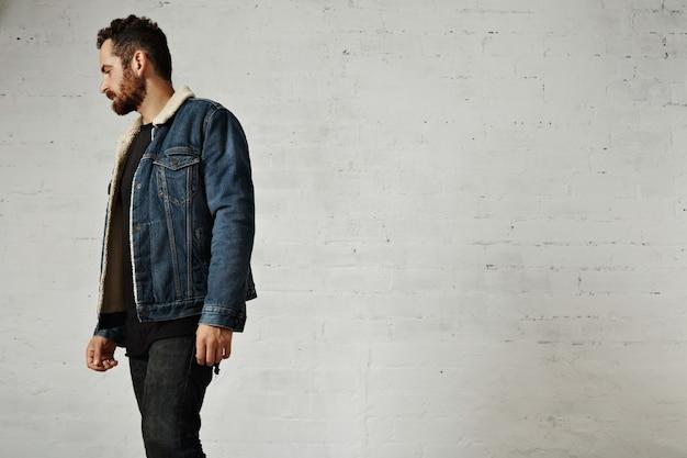 클럽에서 흰색 벽돌 벽에 고립 된 아름 다운 수염 난된 남자 weared 양모 데님 재킷과 검은 색 빈 옷