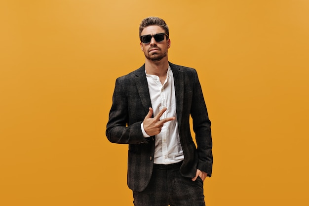 Beautiful bearded stylish man in checkered suit, trendy white shirt and sunglasses shows three fingers and poses on orange wall.