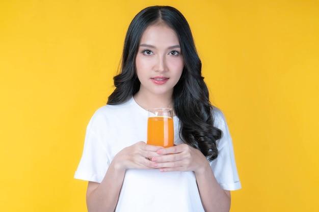 美しい美しさアジアの女性かわいい女の子は白い背景の上の健康のためにオレンジジュースを飲んで幸せを感じます-ライフスタイルの美しさの女性の健康的なコンセプト