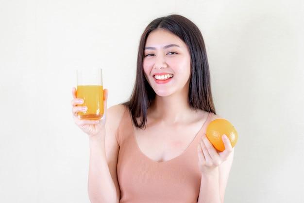 美しい美しさの女性アジアのかわいい女の子は午前中に健康のためにオレンジジュースを飲んで幸せを感じる