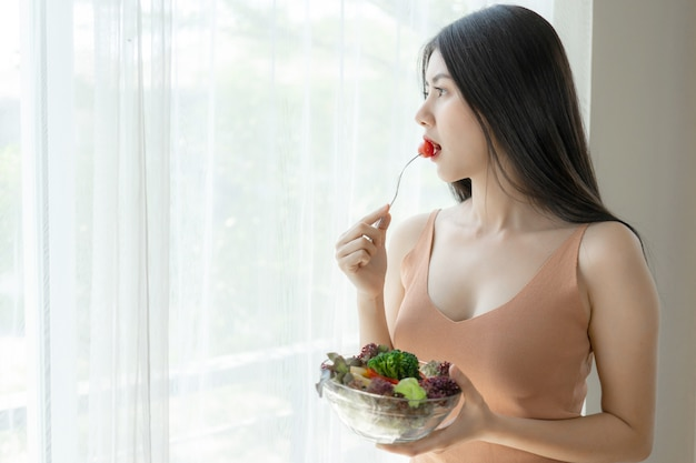 Beautiful beauty woman asian cute girl feel happy eating diet food fresh salad for good health in the morning