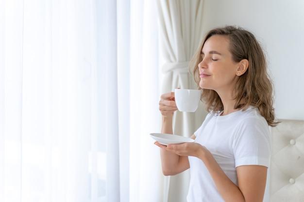 Красивая женщина красоты милая девушка чувствует себя счастливой пить кофе утром