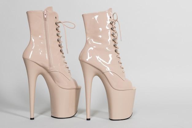 Красивые бежевые блестящие туфли для танцев на пилоне или стриптиза на сером фоне