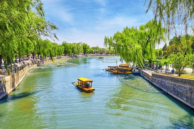 Beautiful beihai park boat on a pond with peoples near the forbidden city beijingchina