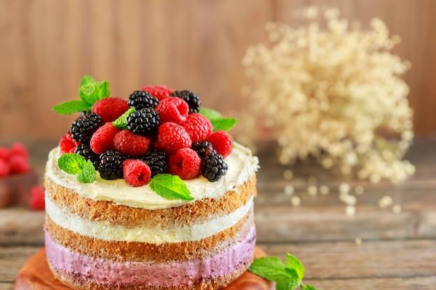 Красивый ягодный торт, украшенный свежей малиной и ежевикой на деревянных фоне.