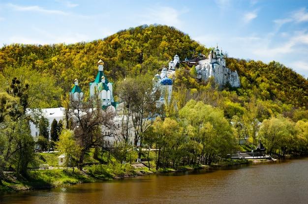 晴れた秋の暖かい日には、緑の茂みで覆われた丘の上の川のほとりにある正教会と修道院の美しい魅惑的な景色。精神的な生活の概念