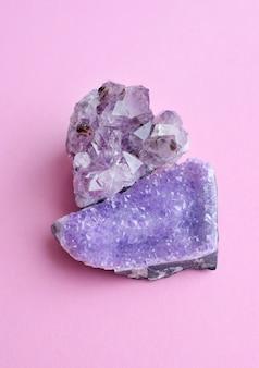 Красивые большие кристаллы аметиста на розовой поверхности