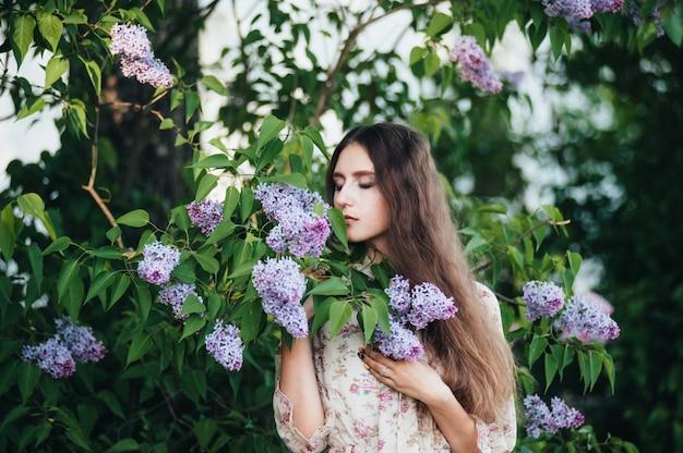 Beautiful big-eyed girl near the lilac tree.