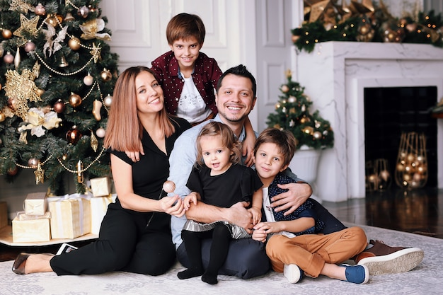 Beautiful big family spend time at home near the christmas tree